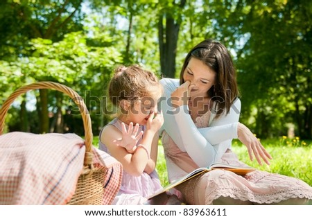 Mother with child are playing while reading book and imitating elephant - stock photo