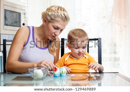 mother with child boy decorate easter eggs