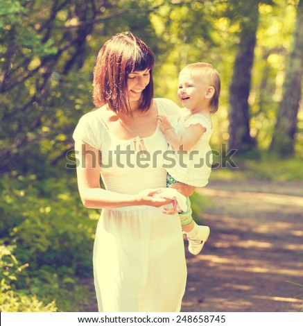 Mother with child happy family outdoors summer time in green garden playing - stock photo