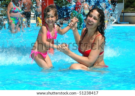 Mother with child in water pool - stock photo