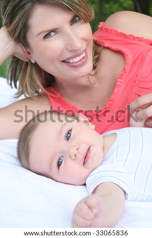Mother with child (infant baby boy son) smiling and happy - stock photo
