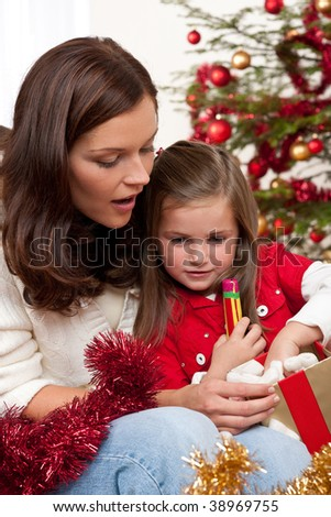 Mother with child opening present on Christmas
