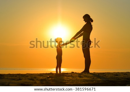 Mother with child sit on the beach at sunset in the summer and look at each other - stock photo