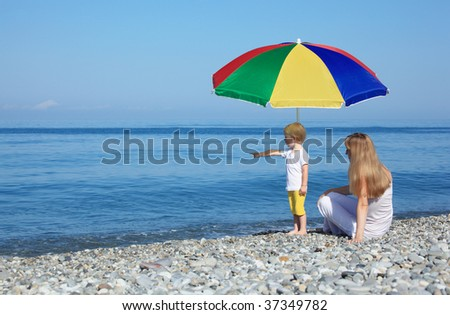 Mother with child under colored umbrella on pebble beach - stock photo
