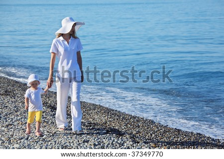 Mother with child walk on edge of sea - stock photo