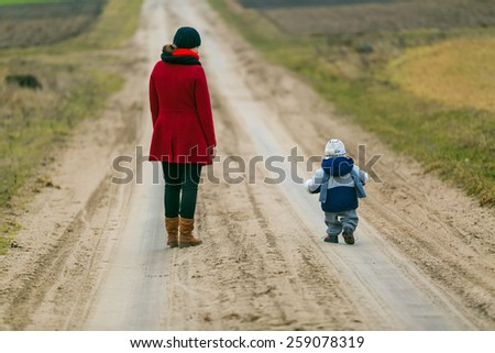 Mother with child walking by rural sandy road - stock photo