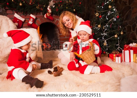 Mother with children are sitting near fireplace and play with cones - Christmas decorations - stock photo