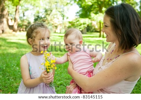 Mother with children having happy time - gilr with flowers - stock photo