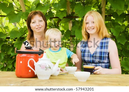 mother with children having tea at pergola - stock photo