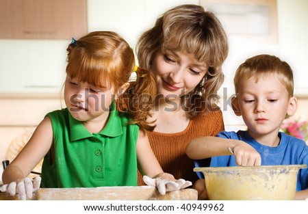 Mother with children in kitchen - stock photo
