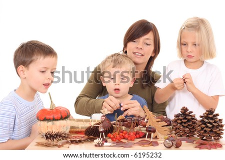 mother with children making autumn decoration isolated on white