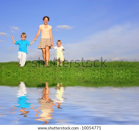 mother with children on meadow and water - stock photo