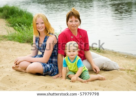 mother with children on river beach in summer - stock photo
