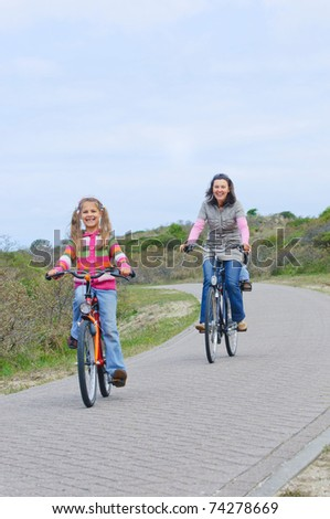 Mother with children on their bikes - stock photo