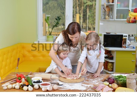 mother with children prepare dough for pizzas