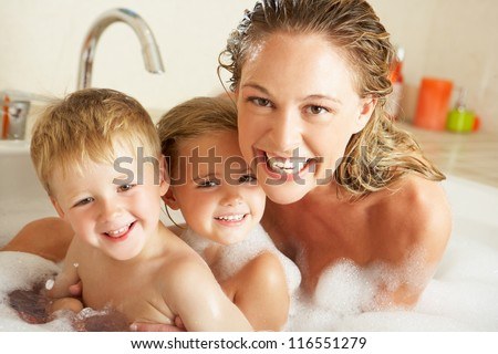 Mother With Children Relaxing In Bubble Filled Bath - stock photo