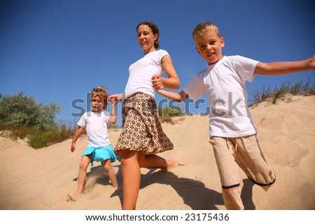 Mother with children runs on sand