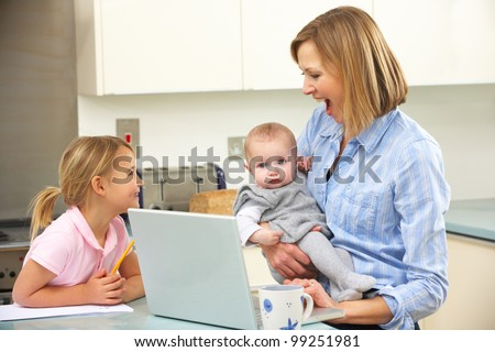 Mother with children using laptop in kitchen - stock photo