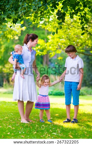 Mother with children walking in the park on a very warm sunny summer day at sunset with beautiful clothes and adorable daughter, newborn son and his older teen age brother holding hands and giggling - stock photo