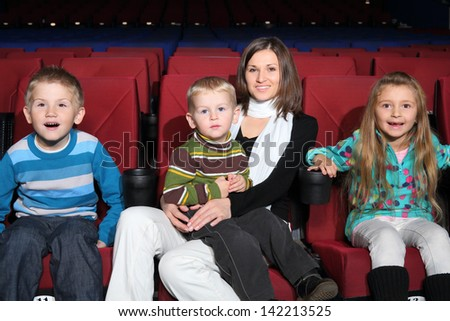Mother with children with admiration watching a movie in the cinema - stock photo