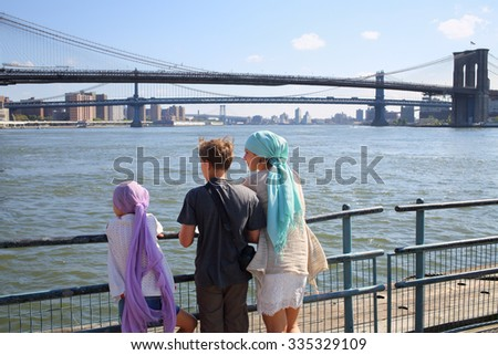 Mother with daughter and son standing on a pier in front of bridges, view from the back - stock photo
