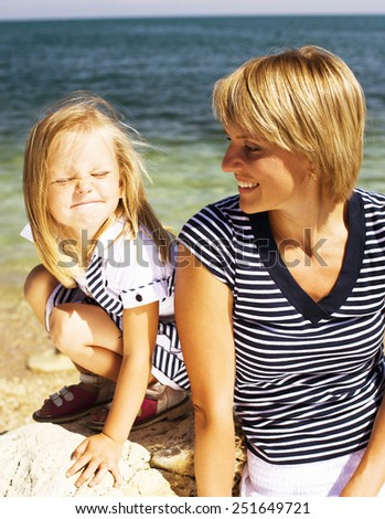 mother with daughter at sea cost together, happy family - stock photo
