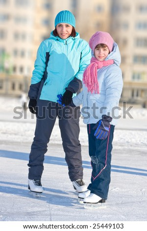 Mother with daughter at the skating rink. - stock photo