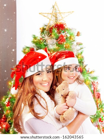 Mother with daughter celebrate Christmas, pretty woman with baby girl near Xmas tree isolated on white background, happy New Year party at home