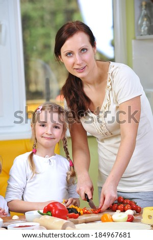 mother with daughter cut vegetables for pizzas