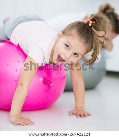 Mother with daughter doing gymnastic exercises with balls - stock photo