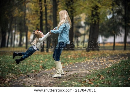 Mother with daughter in autumn park - stock photo