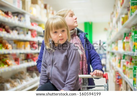 Mother with daughter in shopping cart select products on shelves in supermarket