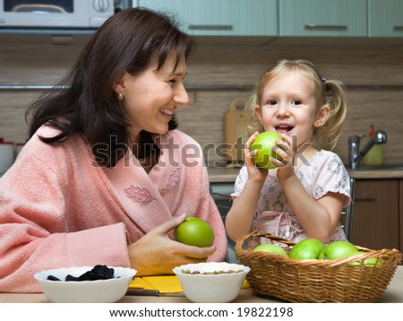 Mother with daughter  is eaten fruit in kitchen