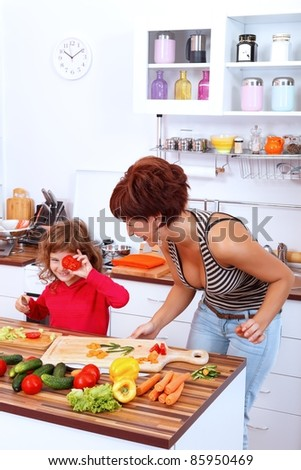 Mother with daughter laughing in the kitchen - stock photo