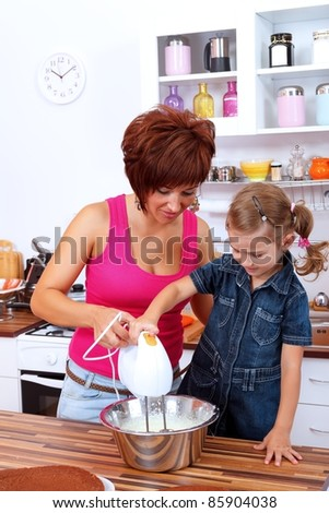 Mother with daughter making cream together - stock photo