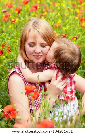 Mother with daughter on the poppy meadow