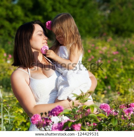 Mother with daughter on the rose flower field - stock photo