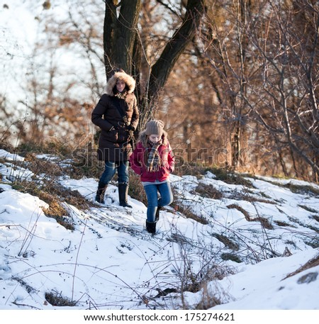 Mother with daughter on the walk in winter park - stock photo