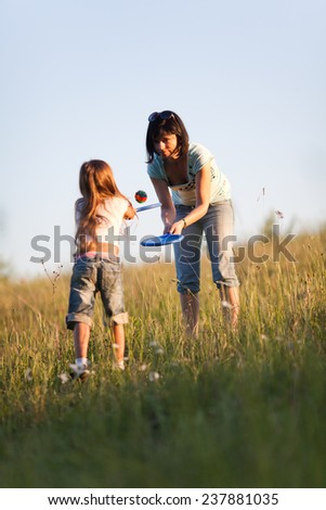 Mother with daughter playing tennis on the lawn in evening light - stock photo