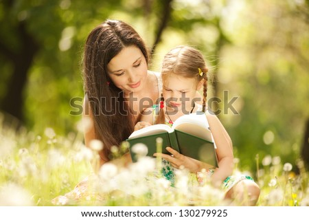 Mother with daughter read a book in the park
