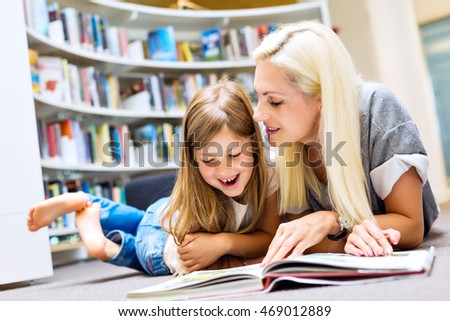 Mother with daughter read book together in library. Happy family, preschool concept. Parent educating children.