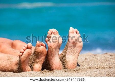 Mother with daughter relaxing and sunbathing on a beach - stock photo