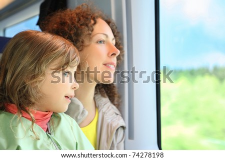 Mother with daughter ride in speeding train - stock photo