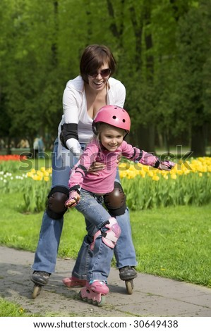Mother with daughter ride rollerblades in the park. Focus on a child