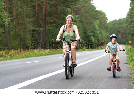 Mother with daughter riding bicycles on a empty road via forrest