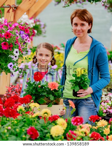 Mother with daughter shopping plants and flowers in garden center