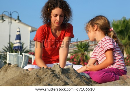 Mother with daughter sit on  beach in  day-time and play on sand - stock photo