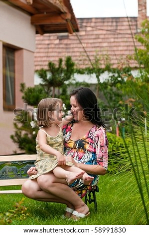 Mother with daughter siting on bench in garden - family house in background
