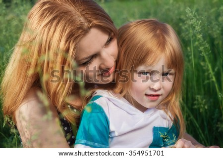 mother with daughter sitting in the green grass - stock photo