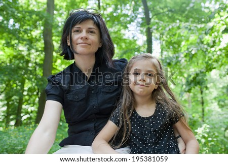Mother with daughter (5-6) sitting on bench at summer park - stock photo